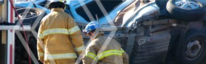 Firefighters looking at rolled over car, car accident attorneys