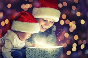 Woman and her Child in santa hats opening gift