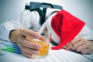 Man in santa hat holding a whiskey over spreadsheets