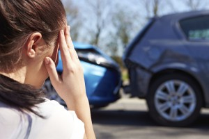 Woman holding head after a rear-end collision, car accident attorneys